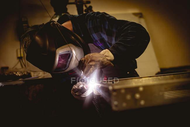Arbeiter, der in der Fabrik an gefertigten Metallteilen arbeitet — Stockfoto