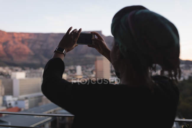 Woman taking photo with mobile phone in balcony. — Stock Photo