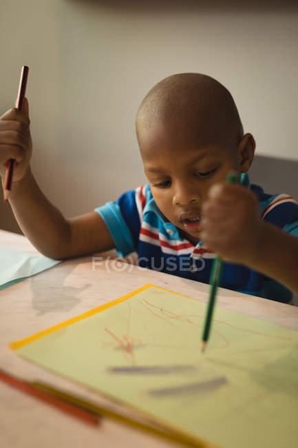 Хлопчик дошкільника малюнок ескіз паперу на столі. — стокове фото