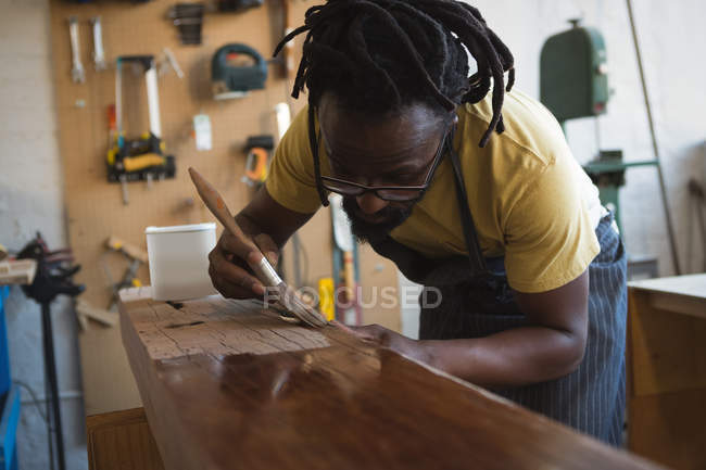 Carpenter painting wooden plank in workshop — Stock Photo