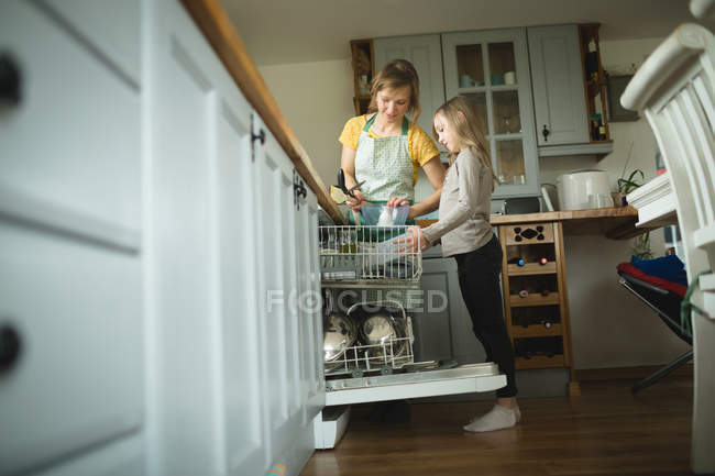 Mother and daughter arranging utensils in kitchen cabinets at home — Stock Photo