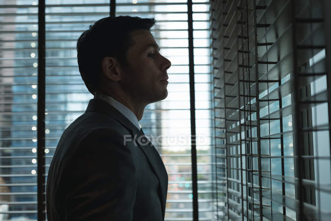 Thoughtful businessman looking through the window — Stock Photo