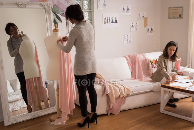 Fashion designer pinning fabric on mannequin in design studio. — Stock Photo