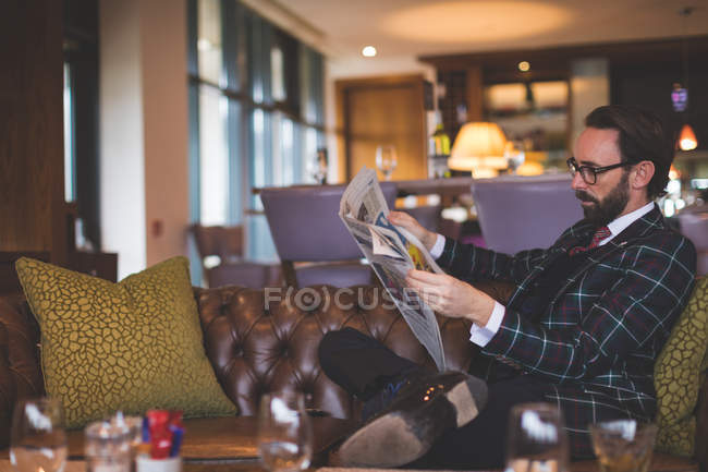 Businessman reading newspaper in hotel — Stock Photo
