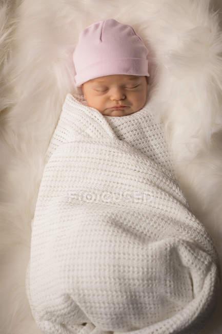 Пеленают новорожденного в шляпе, спать на пушистый одеяло. — стоковое фото