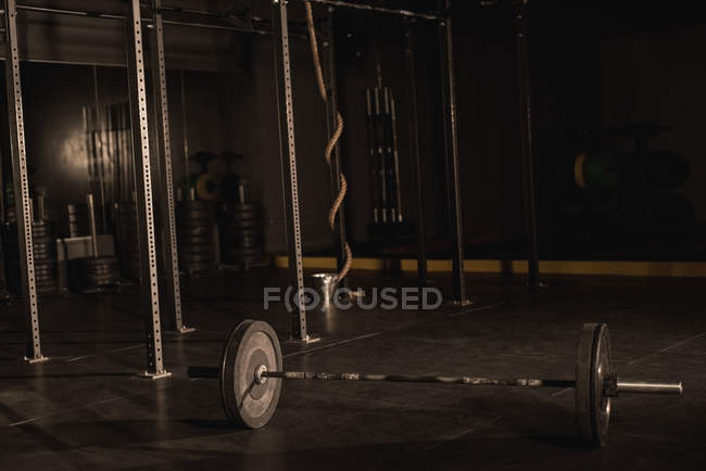Black barbell on a gym floor — Stock Photo