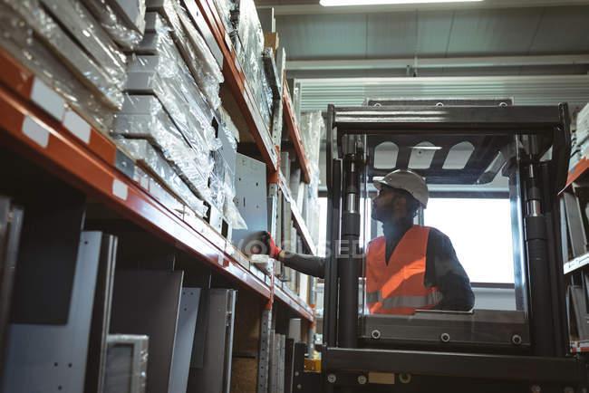 Arbeiter fährt Gabelstapler in Lagerhalle — Stockfoto