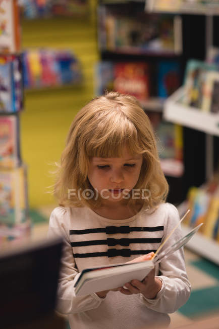 Innocent Girl Reading A Book In Store Stock Photo