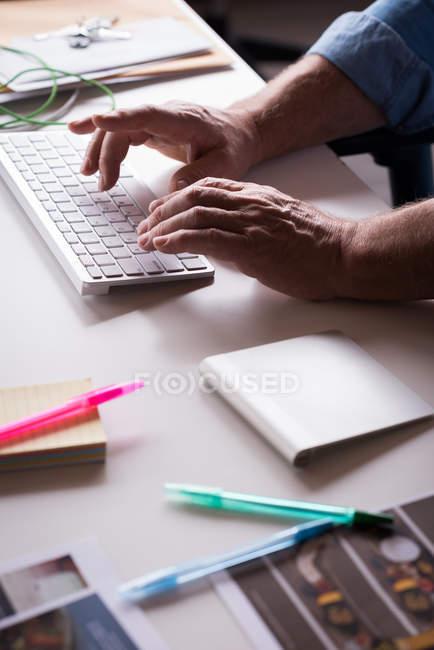 Primo piano dell'uomo d'affari che digita sulla tastiera alla scrivania — Foto stock