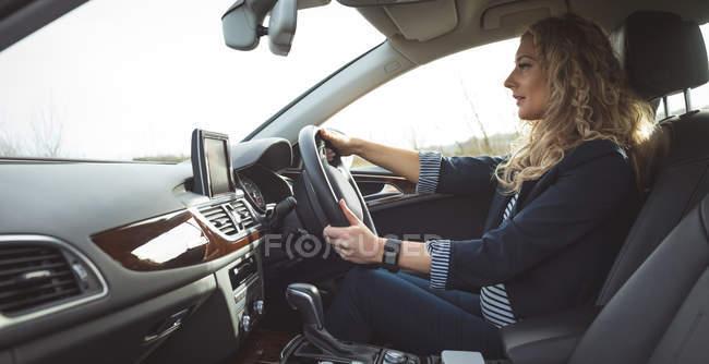 Beautiful female executive driving a car — Stock Photo