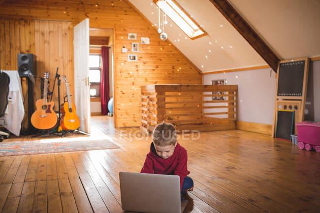 Симпатичный ребенок с ноутбуком на деревянном полу дома — стоковое фото