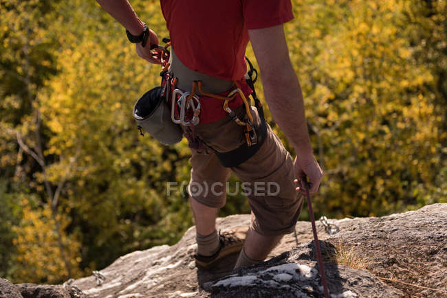 Low section of hiker standing with hiking pole on rocky mountain — Stock Photo