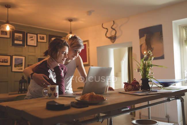 Couple lesbien utilisant un ordinateur portable à la table dans le salon à la maison . — Photo de stock
