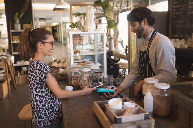 Client ayant effectué un paiement mobile au comptoir au café-restaurant — Photo de stock