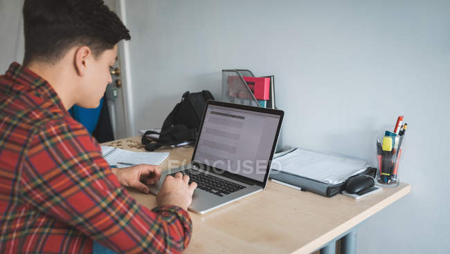 Young man working with laptop at desk at home. — Stock Photo