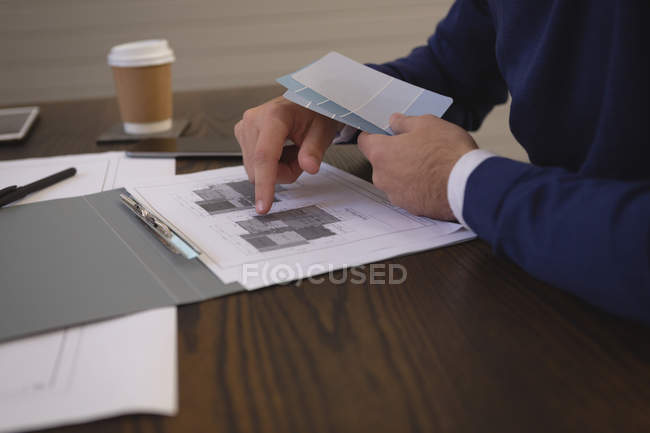 Mid section of businessman discussing and pointing at blueprint at office. — Stock Photo