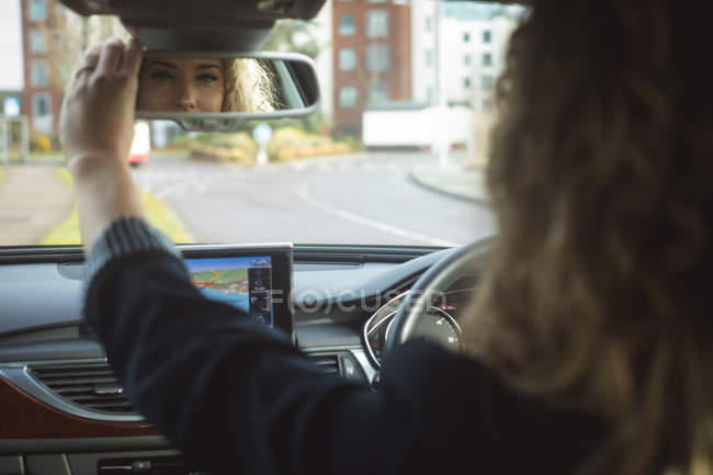 Esecutivo femminile regolazione specchietto retrovisore mentre si guida un'auto — Foto stock