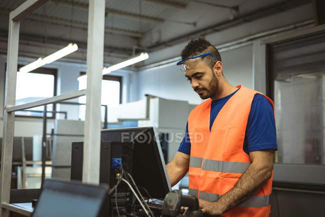 Trabajador masculino que trabaja en la computadora en fábrica - foto de stock