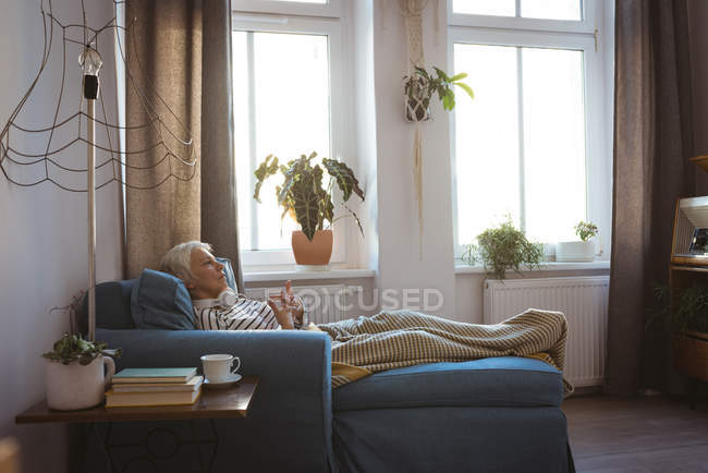 Thoughtful senior woman relaxing on sofa in living room at home — Stock Photo