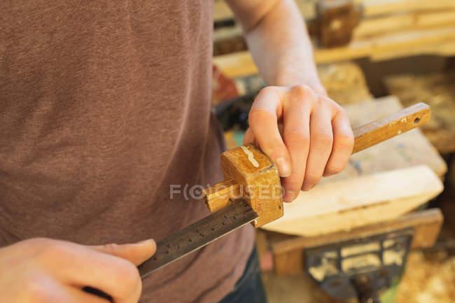 Male carpenter measuring marking gauge with ruler in workshop — Stock Photo