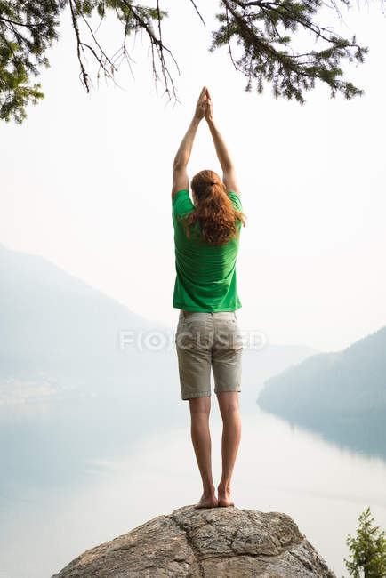 Fit man performing stretching exercise on the edge of a rock at the time of dawn — Stock Photo