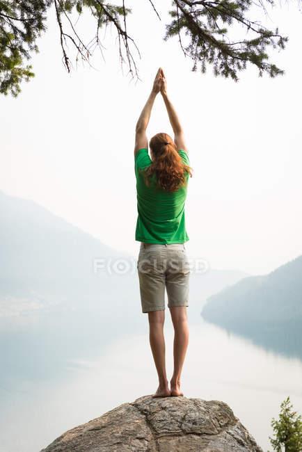 Fit l'homme effectuant des exercice d'étirement sur le bord d'un rocher au moment de l'aube — Photo de stock