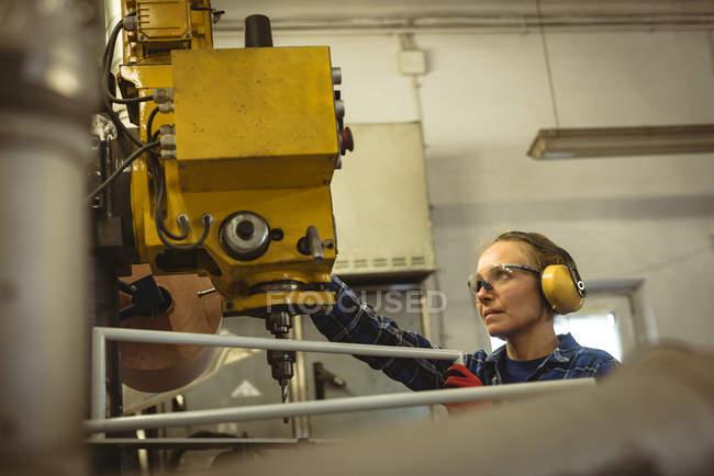 Trabajadora operando una máquina en fábrica - foto de stock