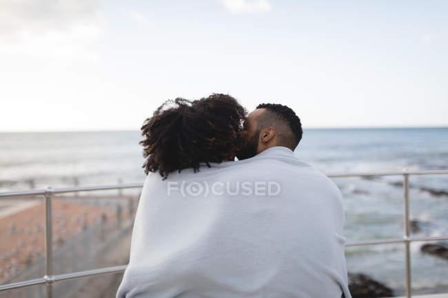 Вид сзади на пару, завернутую в шаль, целующуюся возле пляжа — стоковое фото