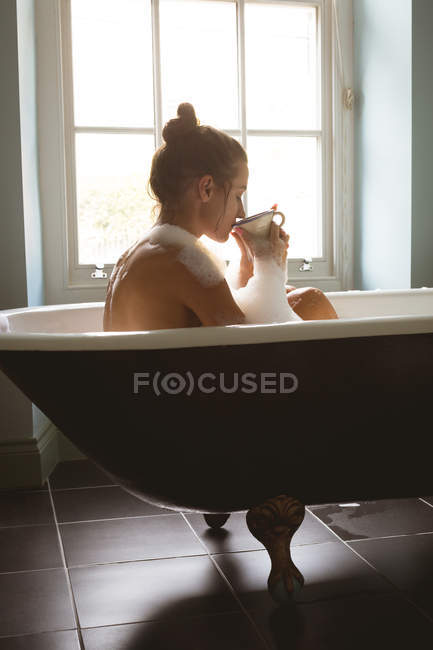 Young woman taking bath in bathtub and drinking coffee. — Stock Photo