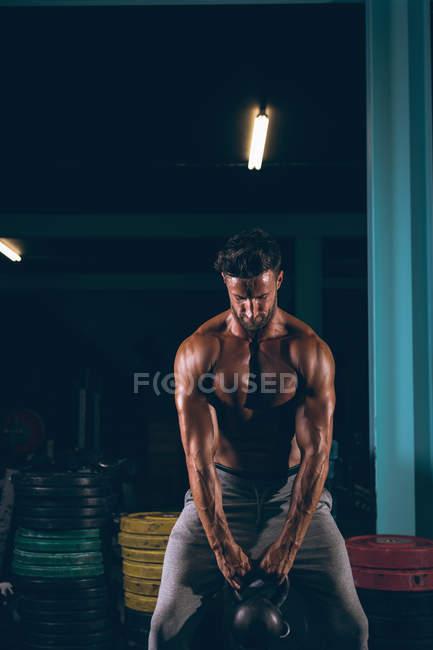 Мускулистый мужчина занимается с гирями в фитнес-студии — стоковое фото