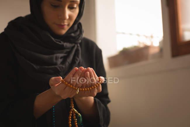 Close-up da mulher muçulmana com grânulos de oração rezando em casa — Fotografia de Stock