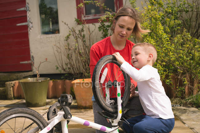 Mother and son repairing bicycle together at backyard — Stock Photo