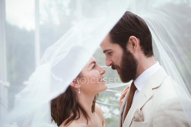 Mariée et marié souriants debout sous le voile — Photo de stock