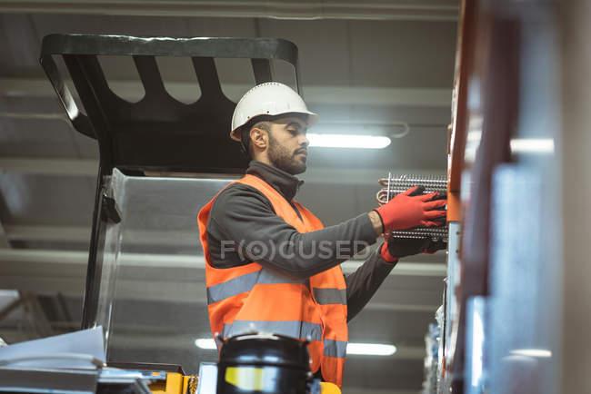 Männlicher Arbeiter überprüft Maschinenteil in Fabrik — Stockfoto