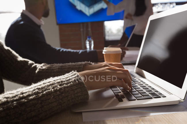 Коллеги по бизнесу работают над ноутбуком в офисе — стоковое фото