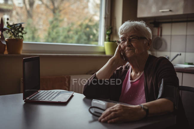 Je pensais femme âgée assise avec une machine à pression artérielle et un ordinateur portable — Photo de stock