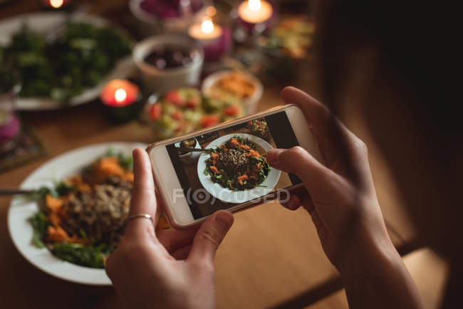 Mulher tirando foto de comida no celular em casa — Fotografia de Stock