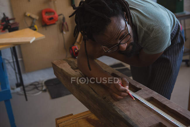 Carpenter measuring wooden plank with tape measure in workshop — Stock Photo