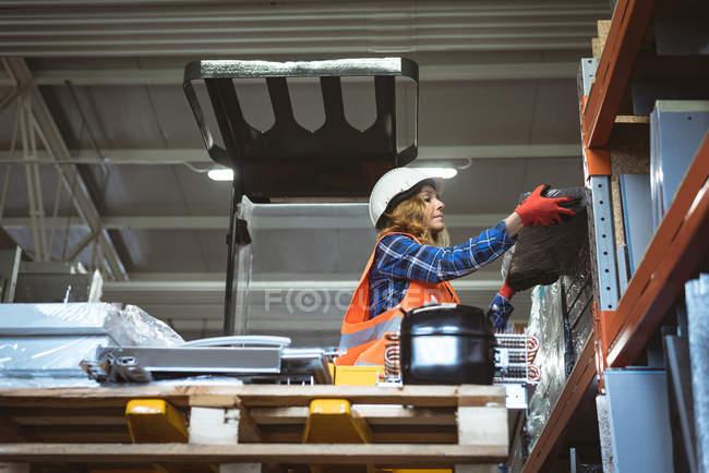 Arbeiterin entlädt Maschinenteil aus Regal in Fabrik — Stockfoto