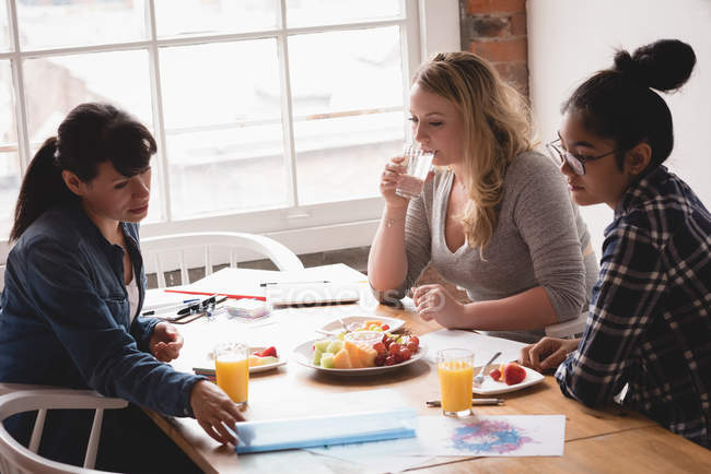 Female executives having breakfast together in the creative office — Stock Photo