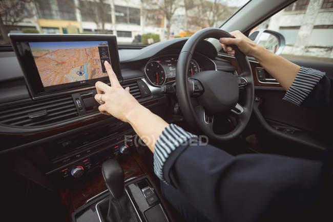 Mujer ejecutiva utilizando la navegación mientras conduce un coche moderno - foto de stock