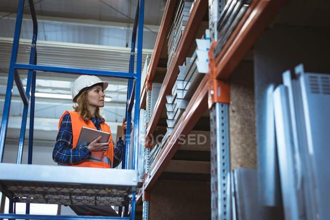 Lavoratrice che mantiene la registrazione su tablet digitale presso il magazzino di fabbrica — Foto stock