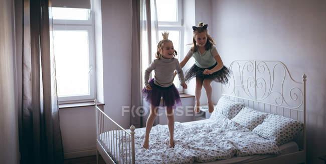 Сестры в костюмах играют на кровати в спальне — стоковое фото