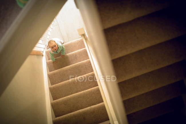 Девочка ползает по ступенькам дома — стоковое фото