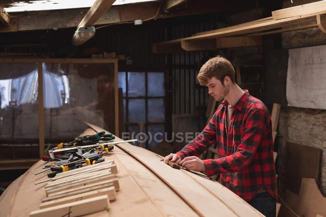 Junge Tischlerin arbeitet in Werkstatt — Stockfoto