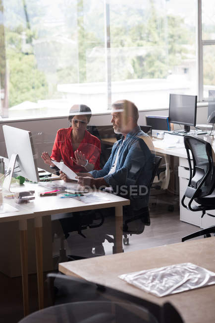 Colegas discutiendo sobre documentos en el escritorio en la oficina creativa - foto de stock