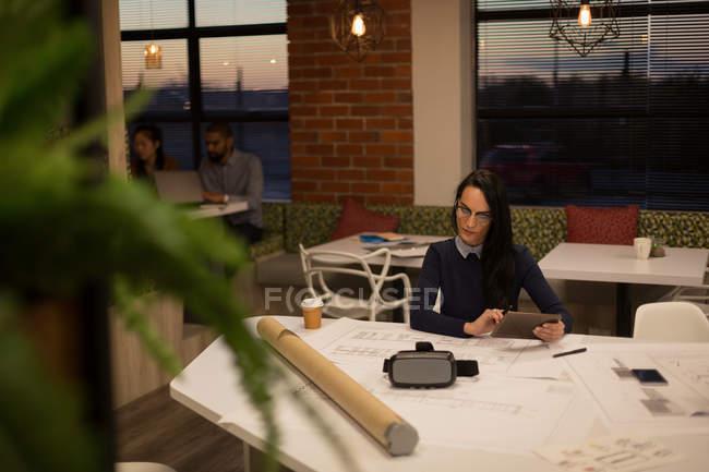 Esecutivo femminile che utilizza tablet digitale in mensa in ufficio — Foto stock