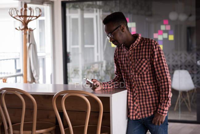 Исполнительный мужского отделения с помощью мобильного телефона в кафетерии творческих отделении — стоковое фото