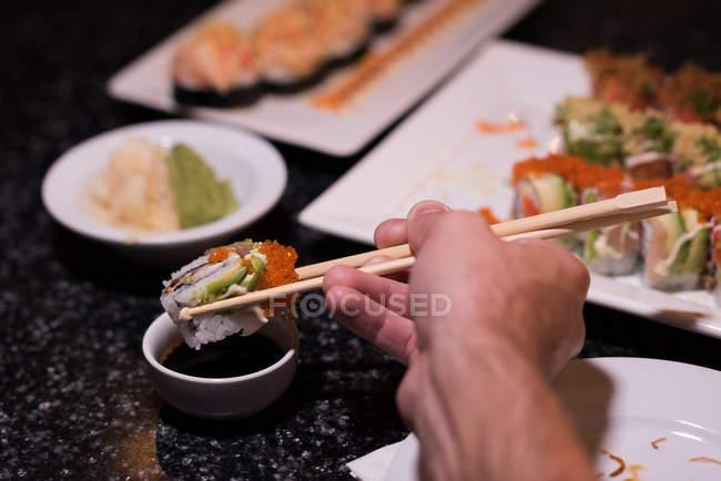 Людина занурення в соєвий соус в ресторан суші — стокове фото