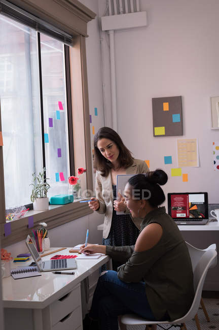 Two fashion designers talking in design studio. — Stock Photo